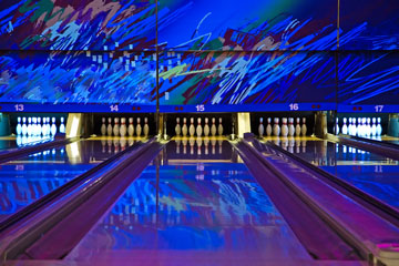 a bowling alley with an abstract wall mural